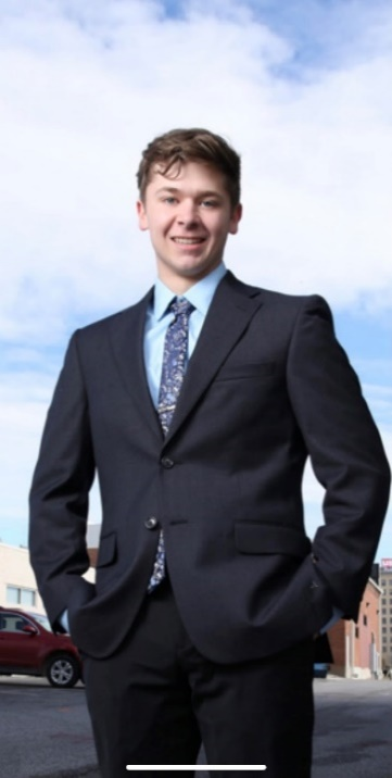 A person in a suit Description automatically generated with medium confidence