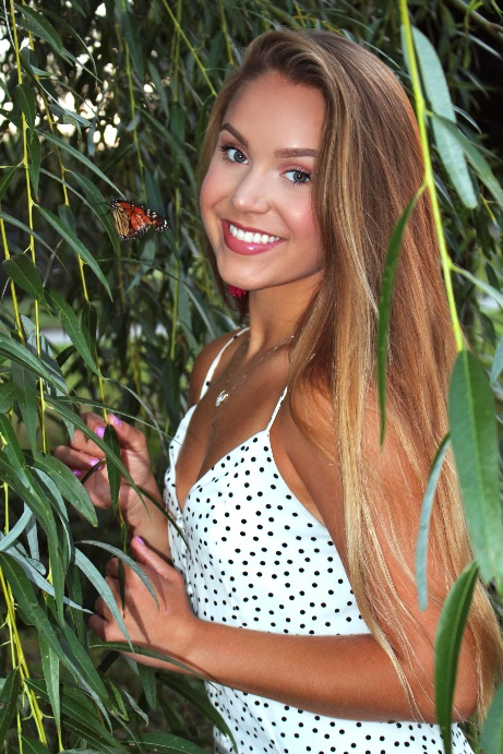 A picture containing outdoor, person, plant, smiling Description automatically generated